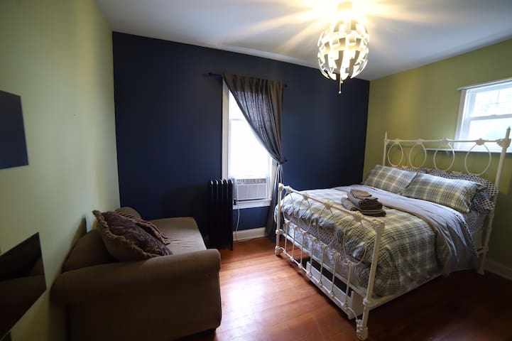 Here's a view of the room from the doorway. There's a dresser next to the door that is not shown here. No curtain on the smaller window. The bed is a full size spring mattress on an antique cast iron frame. Next to the bed is a small table.