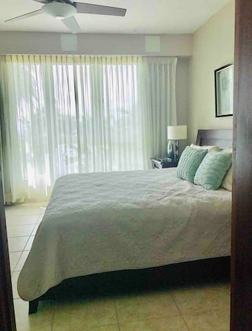 Master Bedroom directly facing the beach and pool area with a private bathroom.   (personal computer, clothes, etc. is located inside - please disregard. thanks in advance)