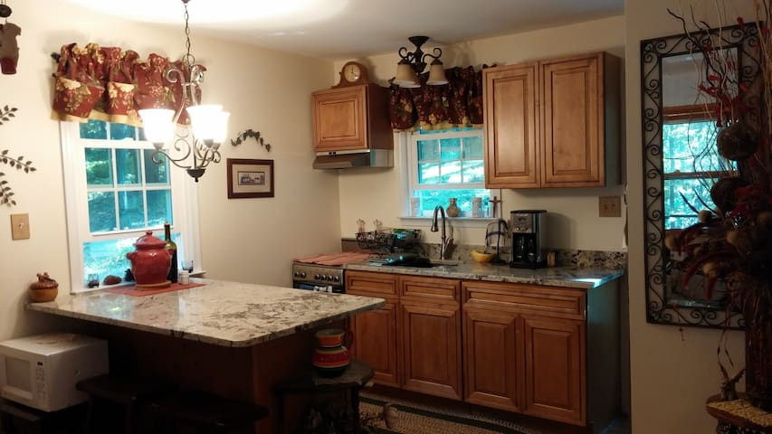 Eat in kitchen with granite counter tops view of the woods and flower bed.