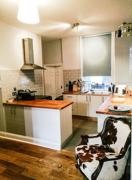 Open-plan, fully equipped kitchen with separate laundry area
