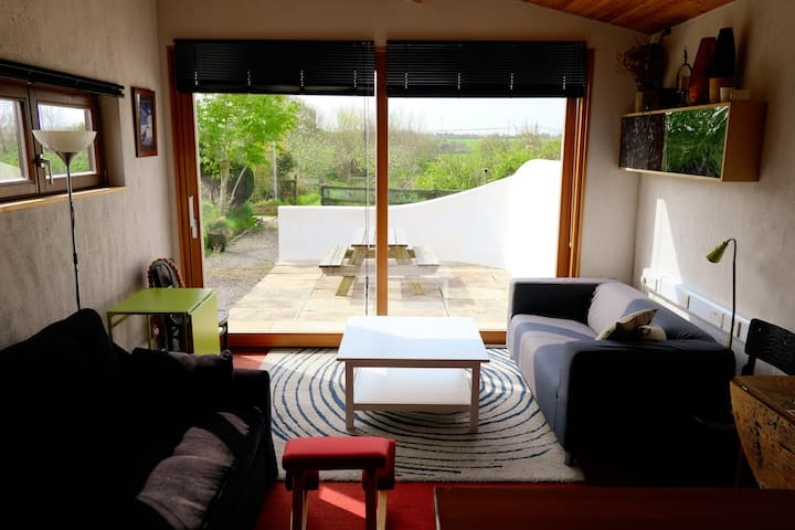 The open plan living area faces into the patio, garden and orchard.