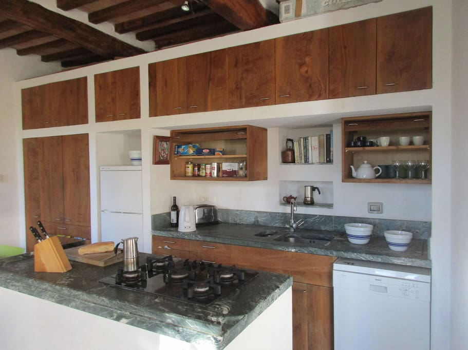 Kitchen, with marble counters, platano cabinets, cooking island.