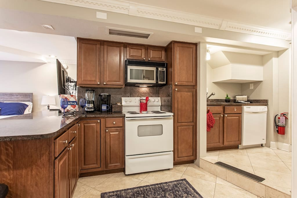 Kitchen is  stocked with pots pans plates and utensils ,  complete with range, microwave, full-size refrigerator and dishwasher !