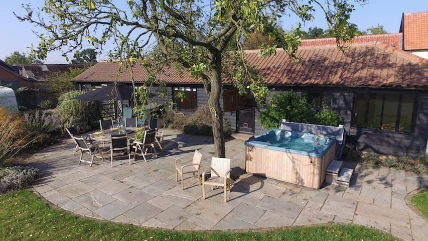 Rear of the barn showing the house, outdoor seating area and hot tub