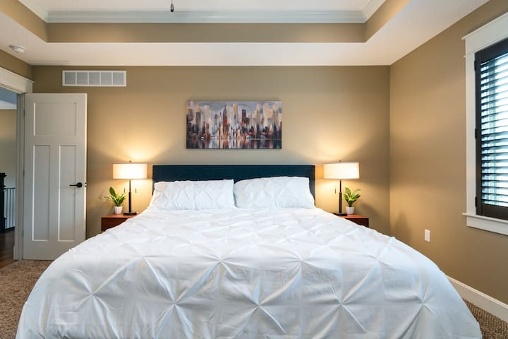 Master bedroom - king-sized bed, usb-charger lamps, and blackout blinds. Perfect setup for great sleep. Ensuite master bathroom attached.