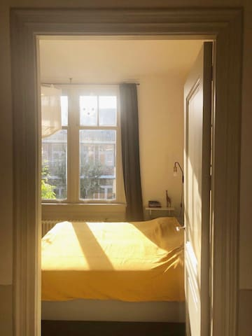 2nd bedroom with double bed; morning light.