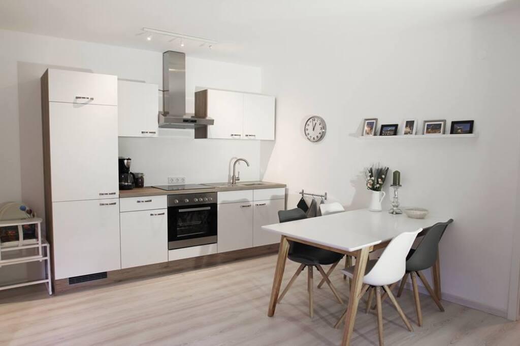 Einbauküche mit Ceranfeld, Backofen, Kühlschrank mit Gefrierfach.