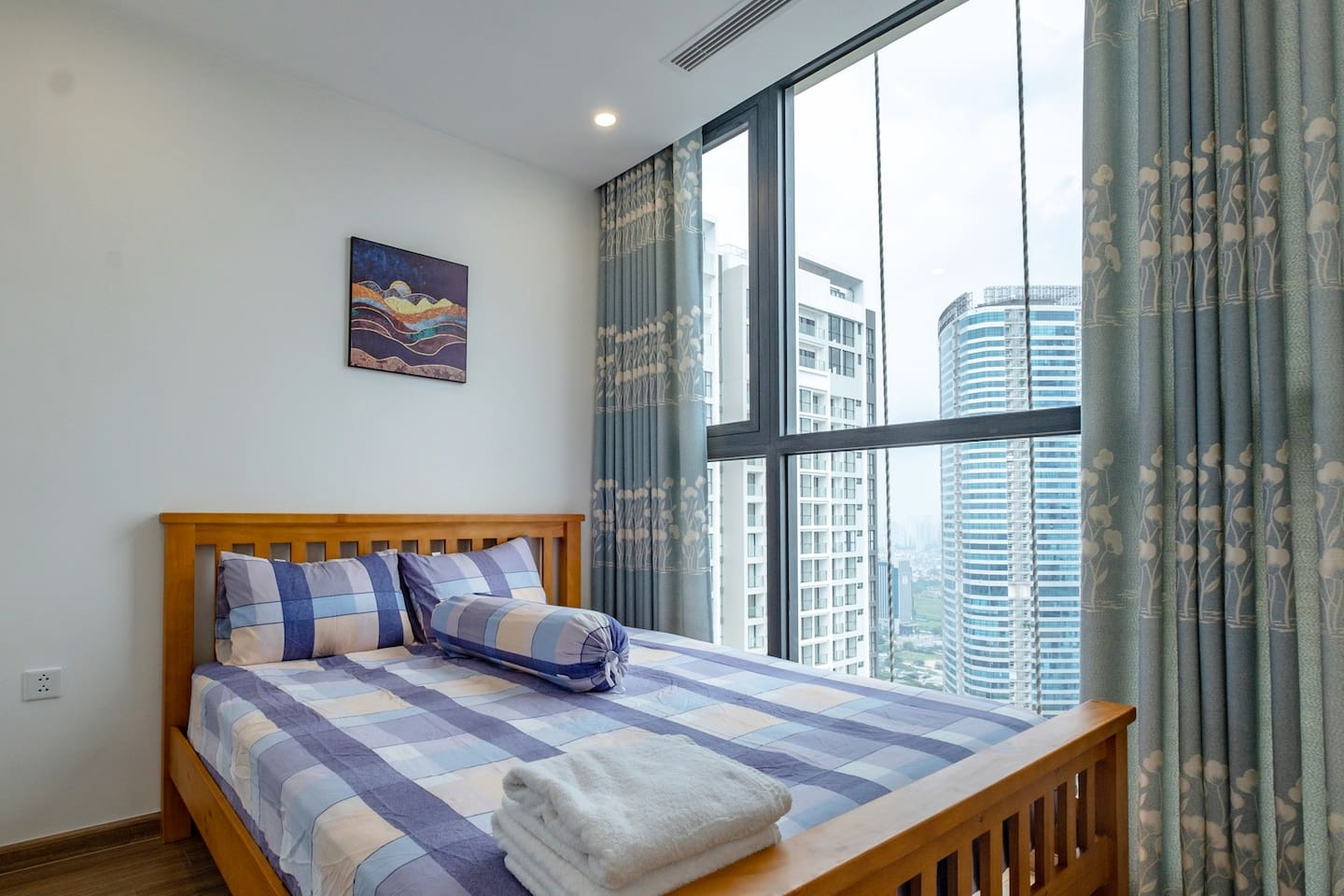 Inside bedroom: queen size bed next to large window. Whether in day or night time, it's relaxing to have such a nice view. The decor is both simple and cozy, to fit in everyone's taste