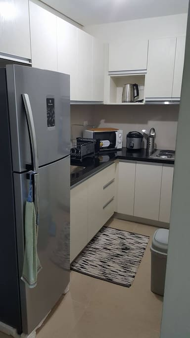 Furnished kitchen with electric stove, exhaust fan, rice cooker, microwave oven, electric kettle, cooking wares, plates, and utensils.