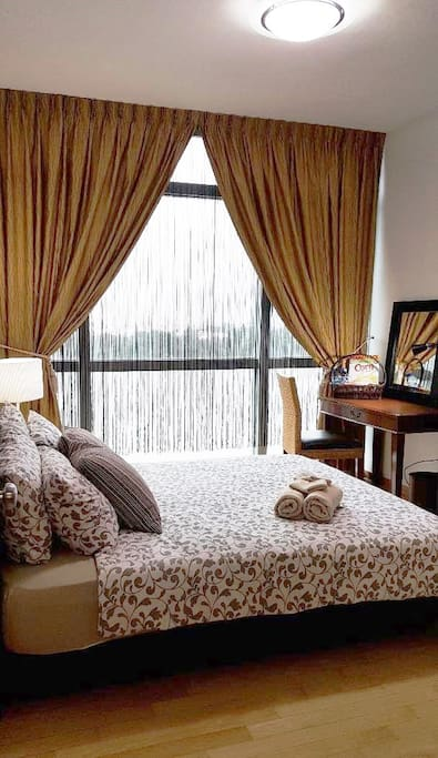 Well Furnished Master Bedroom with String & Night Curtains, Queen Divan Bed with Beddings, Bar Fridge, Table Lamp, Table, Chair, Table Light, Mirror etc.
