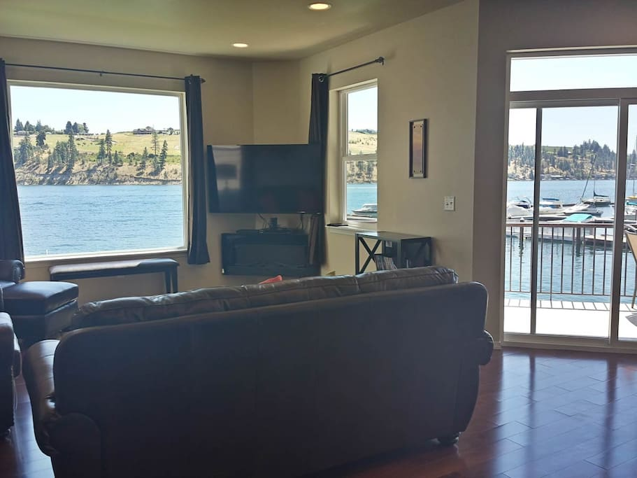 "Large open living room on the main floor with multiple windows and views out to Lake Chelan. Features 60"" flat screen TV and sliding glass door leads out to the covered deck area."