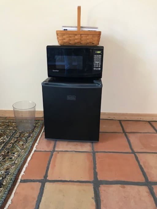 Small refrigerator and microwave. The basket has brochures and local information.