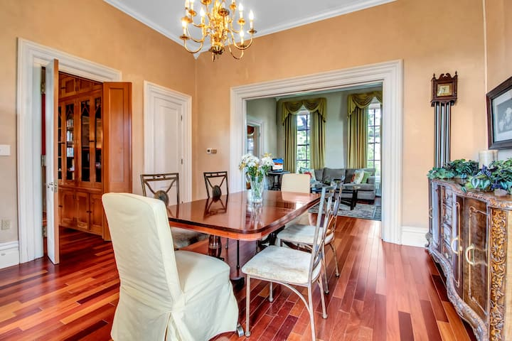 The Formal Dining Room has Plantation Windows with Swagged Drapes and Cherrywood Floors.