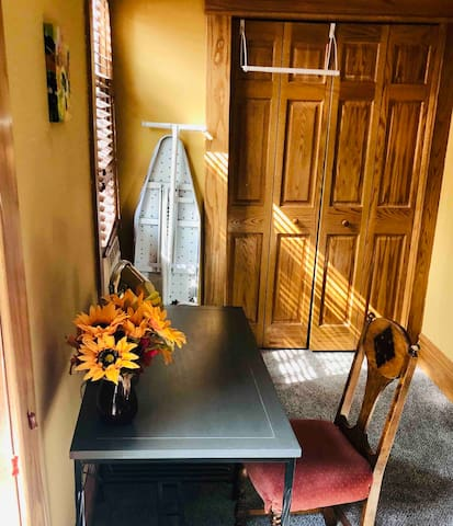 Alcove in the Yellow Room with desk, printer, ironing board, and iron.