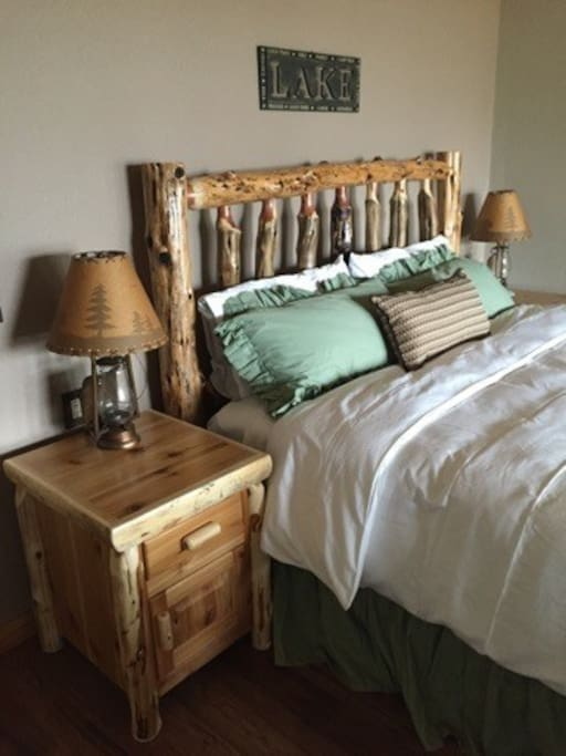 Feel like home with custom log nightstands on either side of the bed accompanied by rustic bedside lamps