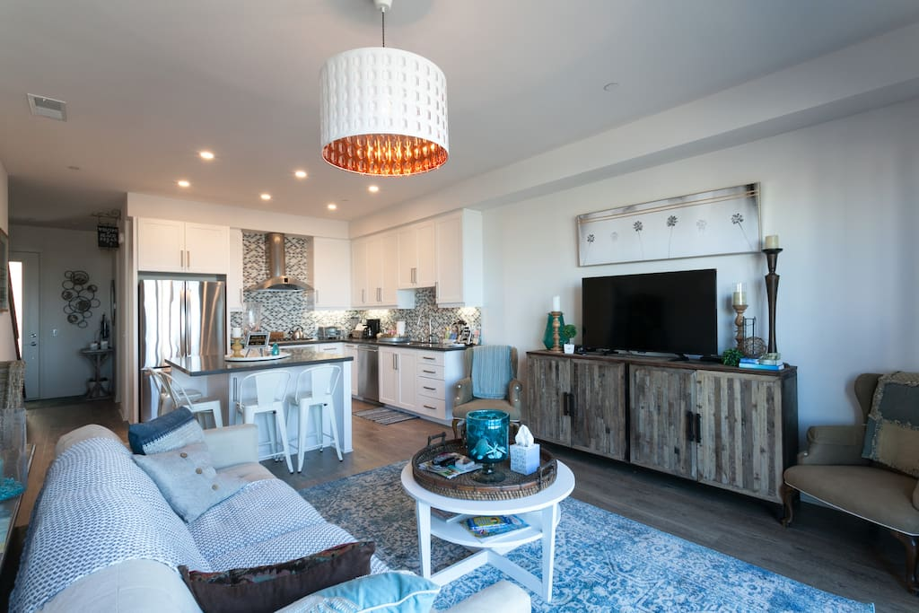 Open concept living with modern beach decor and oceanfront deck