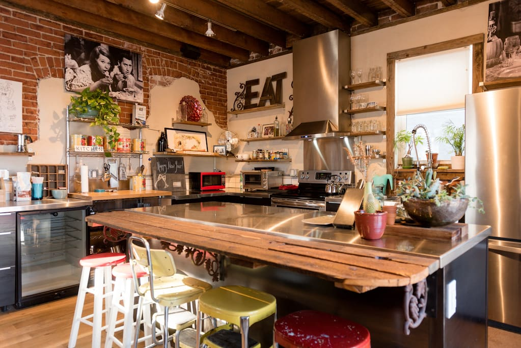 An authentic chef's kitchen -stainless counter tops, exposed wood ceiling with vintage bar stool seating.