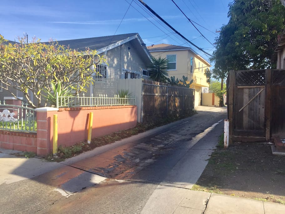 Entering into this alley,  when you see the second house with four car garages, roll up the garage door and park inside the fourth garage which is unlock by the small gate