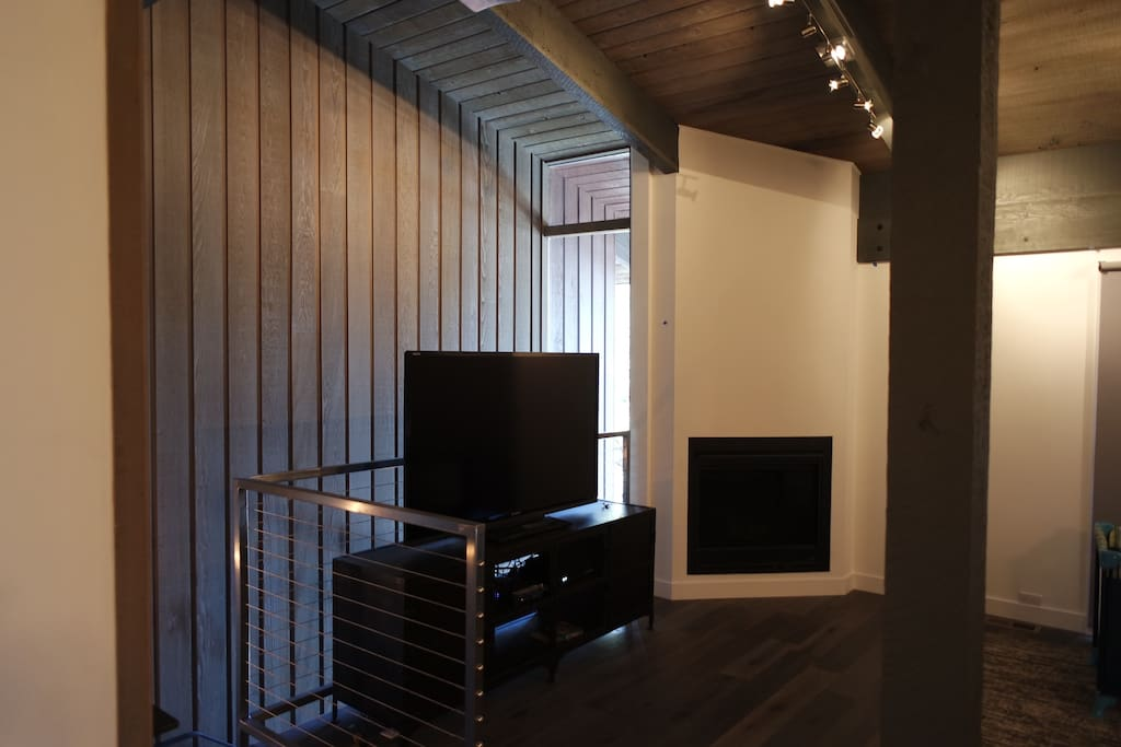 """Living room with 65"""" TV & remote controlled gas fireplace."""