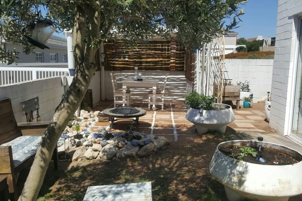 A private garden space with lapa and firepit where our visitors can relax and enjoy the abundant bird life, or sit around a fire in the evening.