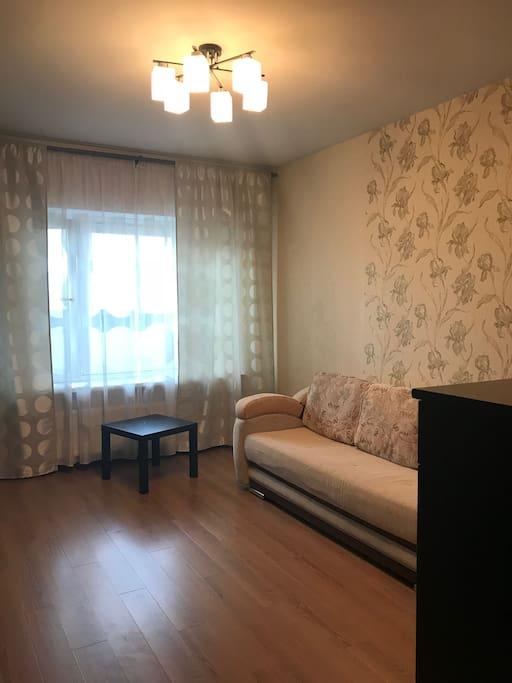 Просторная комната с тв, комодом и большим диваном.