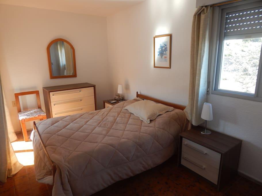 dormitorio con una ventana hacia el puerto y un ventanal hacia el balcón.
