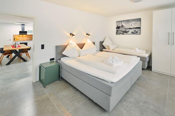 Geräumiges Schlafzimmer - 200x200cm Boxspringbett sowie 80x200cm. Blick in das Wohnzimmer