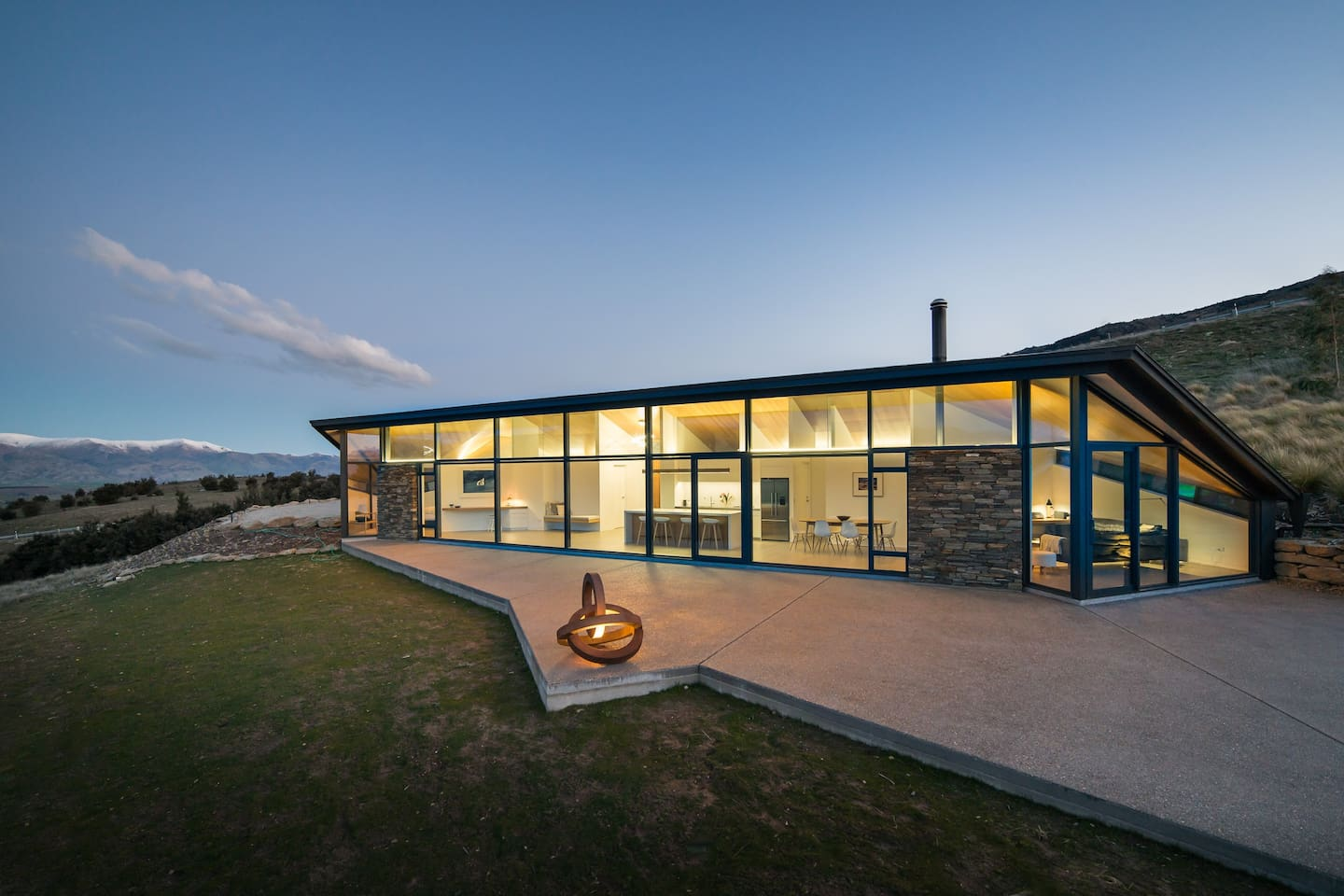 At dusk the strip uplighting makes the house glow. The sculpture, by Auckland artist Neil Donaldson, is called Circles of Life. The stone walls comprise local Schist. There is moveable outdoor furniture to take in the view from any angle.