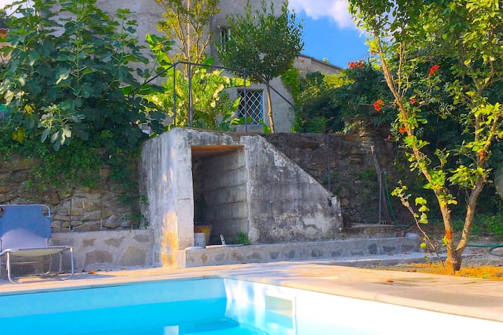 A sunny stone terrace runs the length of the pool, equipped with sun loungers...