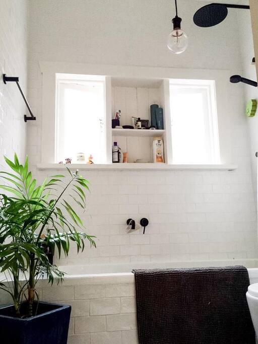 Brand new subway tiled chic bathroom with bath, tall ceiling, hairdryer, hair straightener.