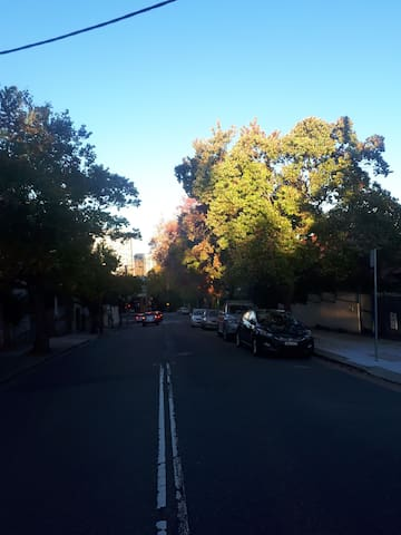 Union st, outside terrace apartment standing on road. Commodore hotel up on the right at the intersection, start of Sydney Harbour Bridge in sight straight ahead (brick)