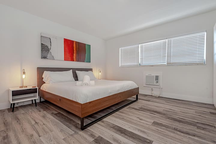 Studio with one queen bed, bathroom and kitchen.