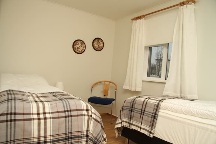 Bedroom 1, two single beds, chair and hanger.