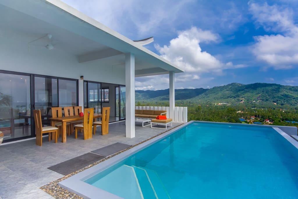 Grande terrasse, table de repas, au bord de la piscine, vue mer