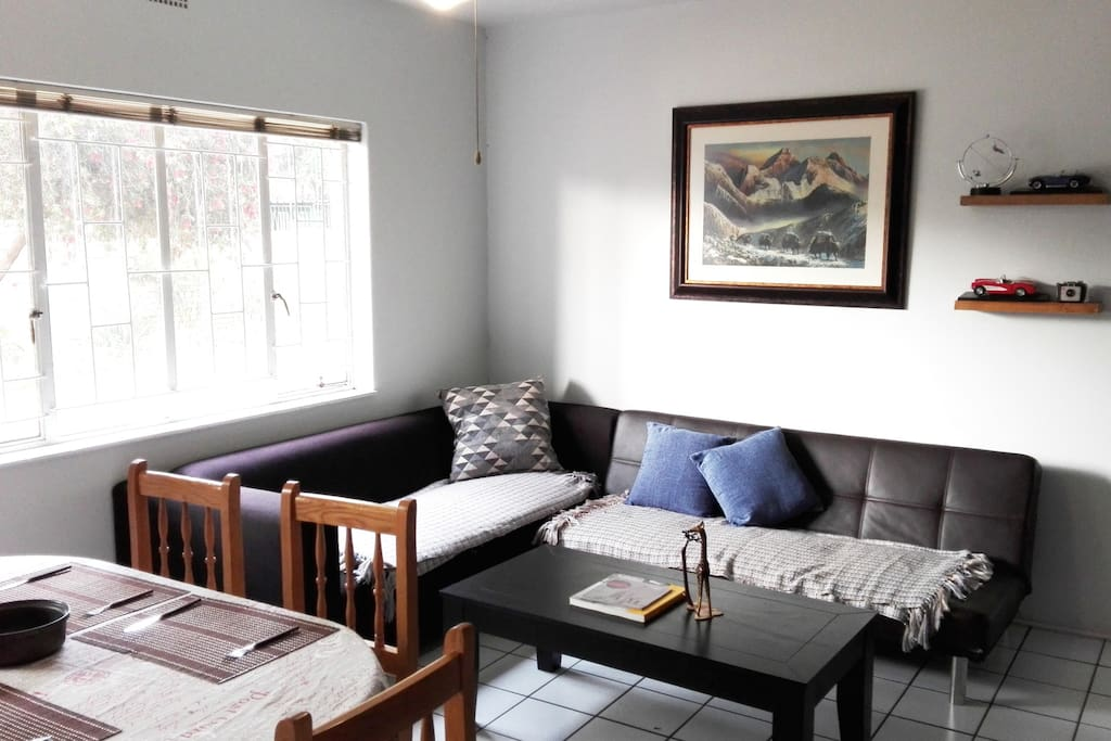 Spacious living area with couches (one sleeper) and dining room table