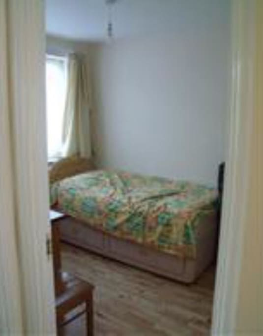 1 bedroom with single bed, desk and basic wardrobe for clothes.