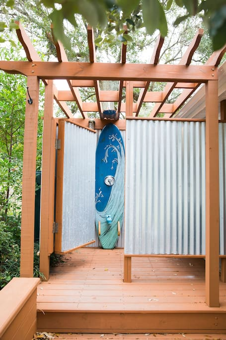 The new outdoor shower with a custom surfboard backdrop painted by local artist Kate Barattini