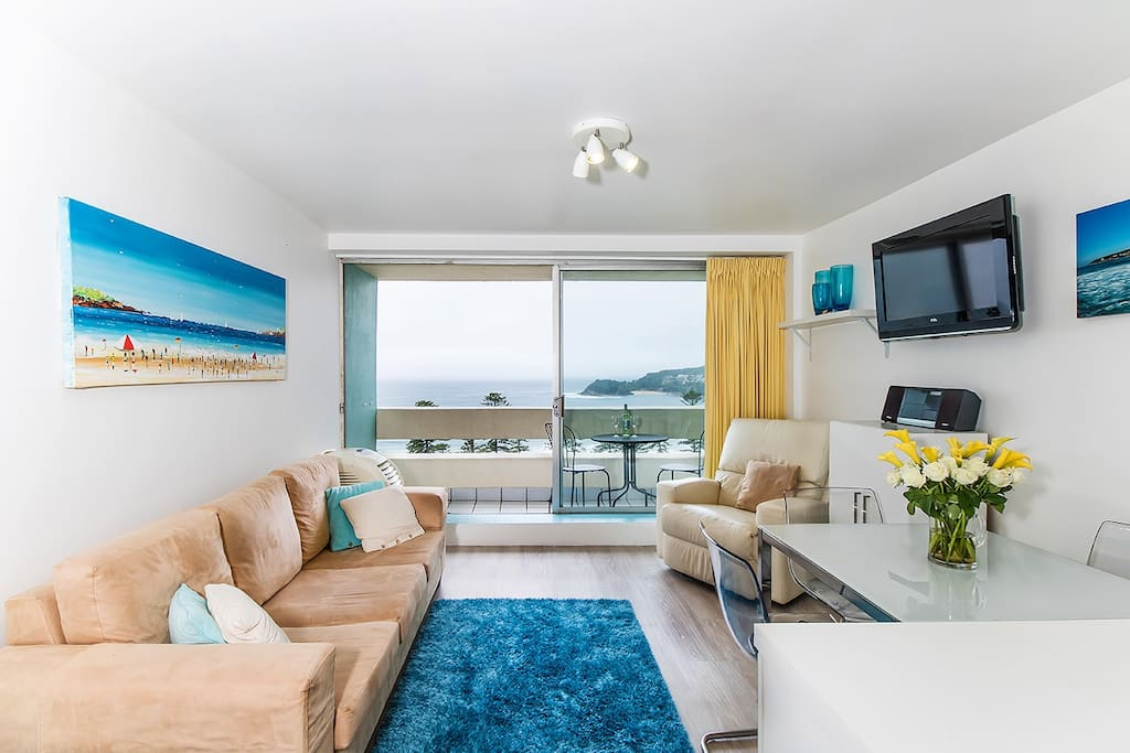 Living room with view to ocean and Manly beach. Leather armchair reclines and the sofa bed is queen size