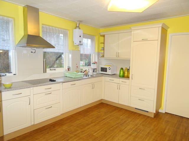 Ruime woonkeuken met inductieplaat en inbouwafwasmachine.