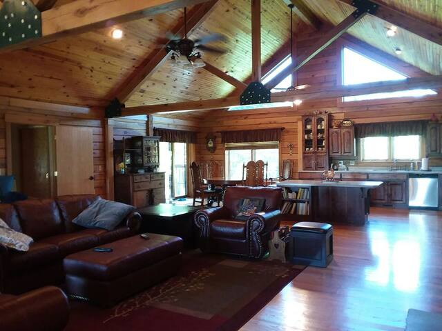 The Great Room featuring a large stone fireplace, beautiful views and a spacious, fully - equipped kitchen. A sliding door leads out to the covered deck and bbq.