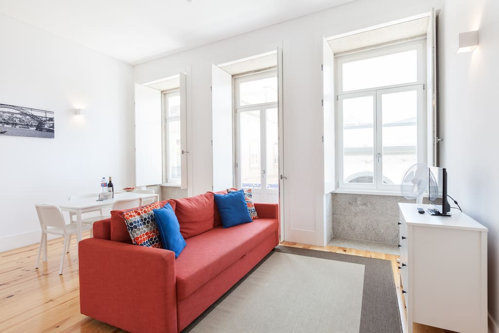 Welcome to this cozy and spacious living room. Big windows and high ceiling in the Oporto Sunset Blue Balcony flat!