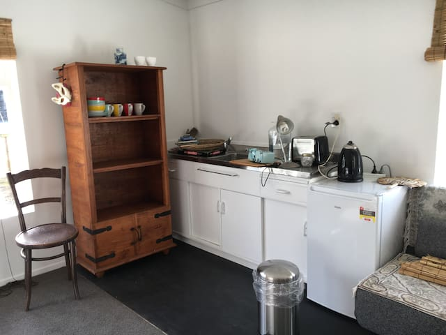 Small kitchen in the room, now with microwave. Soft chair unfolds into single bed.