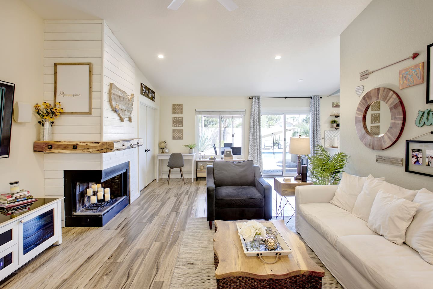 Vaulted ceilings and an open floor plan keep the space light and airy. The fireplace features ship lap and a gorgeous raw edge mantle. Beautiful wood look tile is found throughout the main spaces of the home.