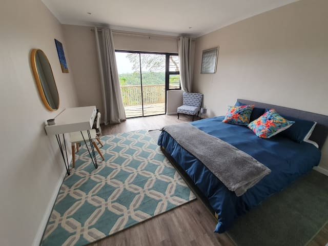 Spacious bedroom with views of the nature reserve out the balcony