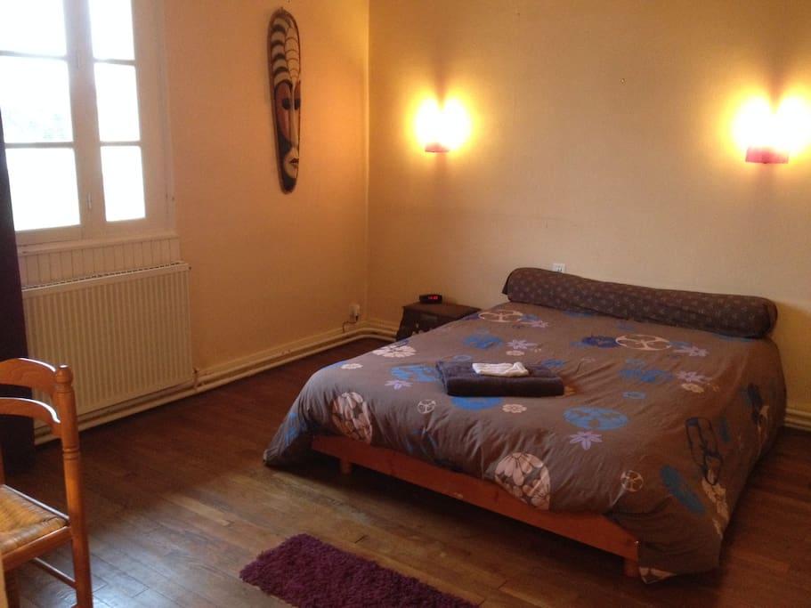 Chambre avec un grand lit 2 place, un dressing, un miroir sur pied et bureau