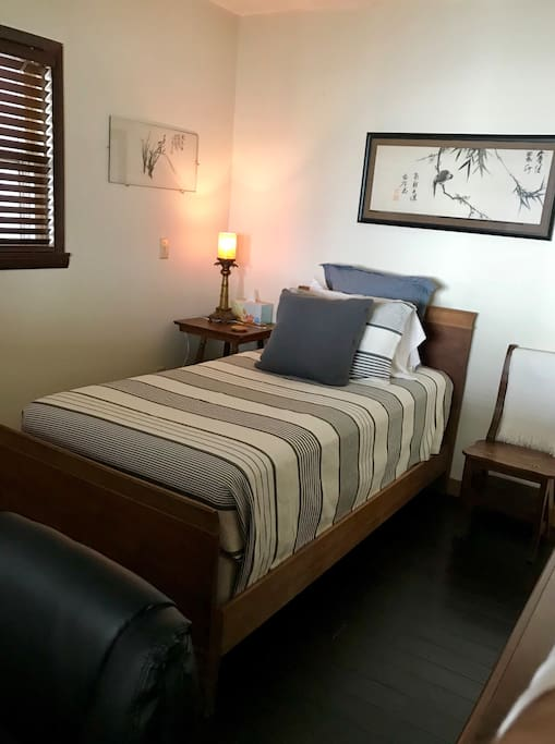 Small guest room with twin bed, built-in desk, closet, locking door. Bed has a firm mattress, lux bedding.
