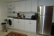 Full kitchen with a stove, microwave, fridge and utensils