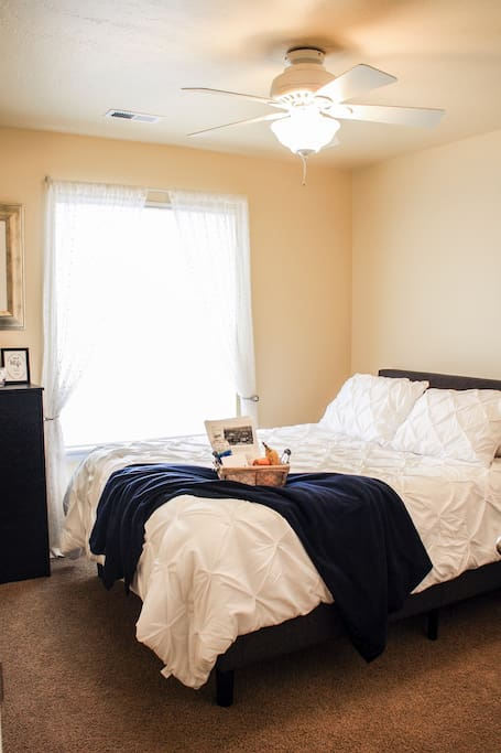 This is the perfect private room for your getaway. Comfortable fluffy queen sized bed with lots of extra blankets. There is dresser storage, a chair, a full mirror, a double door closet with hangers, and a steamer!