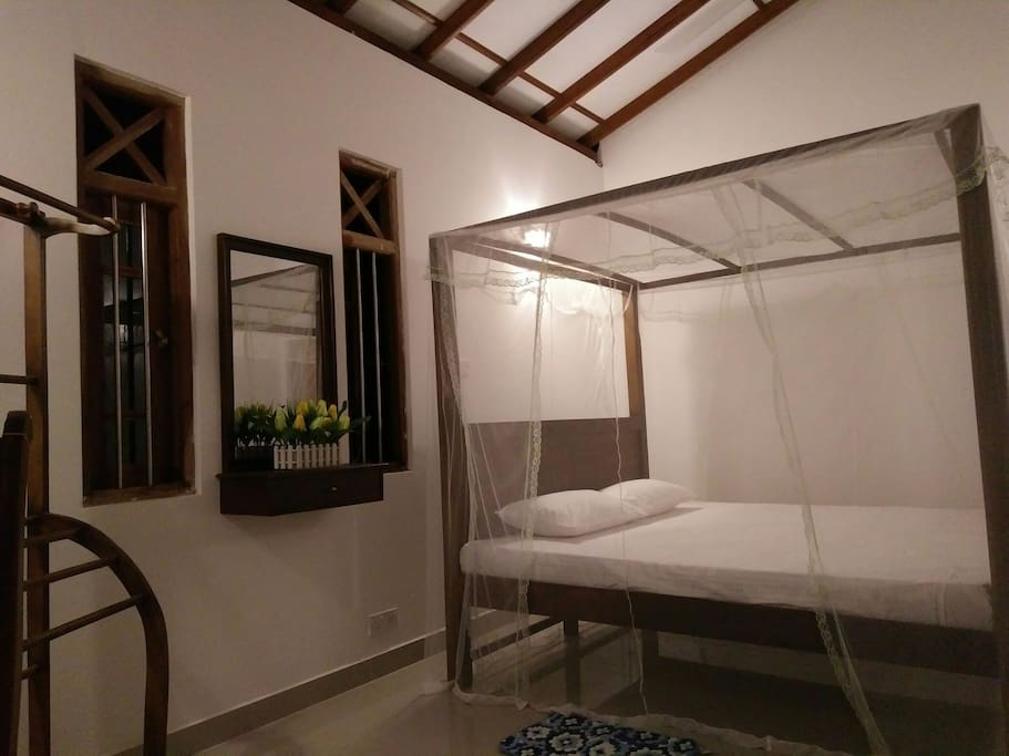 Large balcony view bed room with sri Lankan style queen size bed/clothes rack/mirror and drawer/table and chair