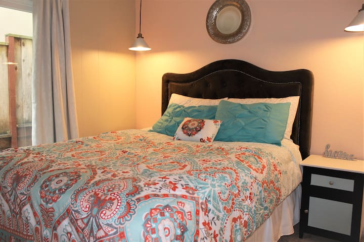 Bedroom number 2: Two pendant lights come down from the ceiling to light the beautiful peach-colored. There are nightstands on each side of the bed.
